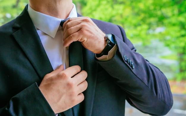 Handen van huwelijksbruidegom die klaar in de bruidegombruid worden die van de kostuumhand op het huwelijk voorbereidingen treffen