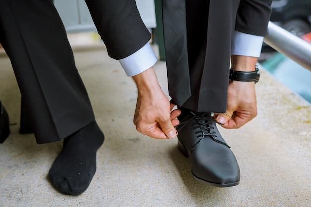 Handen van huwelijksbruidegom die klaar in kostuum worden die zijn huwelijksschoenen zetten.