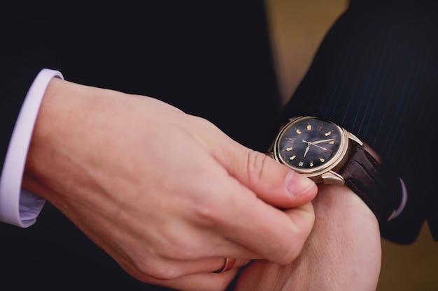 Handen van huwelijksbruidegom die zich klaar maken in pak