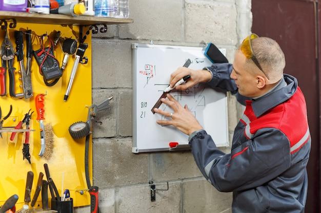 Handen van ingenieur tekenen met potlood aan boord