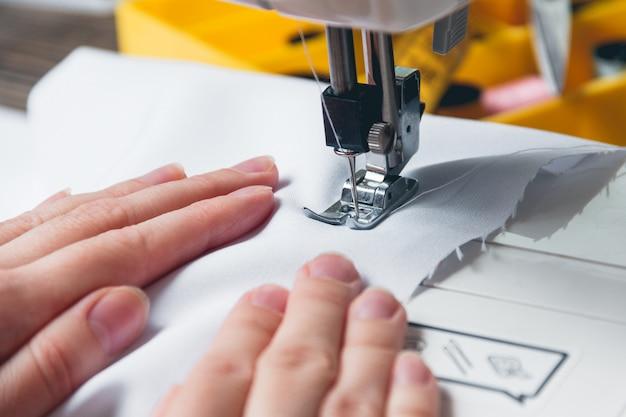 Handen van jong meisje op naaimachine