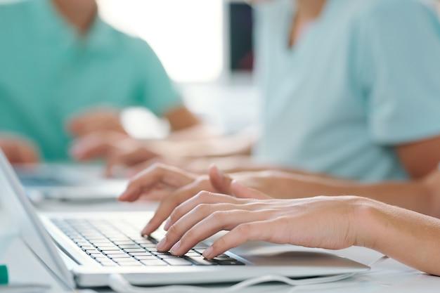Handen van jong wijfje of schoolmeisje over toetsenbord van laptop tijdens werk over project of presentatie