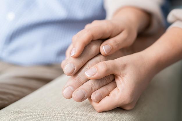 Handen van jonge aanhankelijke en zorgvuldige dochter die die van haar oudste vader vasthoudt die liefde en saamhorigheid uitdrukt
