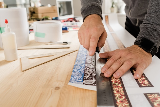 Handen van jonge ambachtsman of ontwerper door houten tafel die liniaal en mes gebruikt om versierd papier te snijden om kragen te maken
