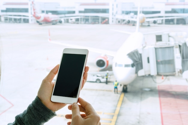 Handen van jonge aziatische vrouw die slimme telefoon met behulp van aan vdo-oproep met haar familie door het venster terwijl het wachten op instaptijd bij luchthaven. close-up, kopieer ruimte