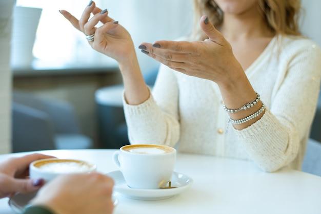 Handen van jonge casual vrouw met armbanden aan tafel zitten en iets uit te leggen aan haar vriend tijdens gesprek