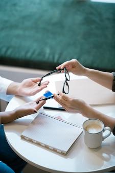 Handen van jonge cliënt van optische klinieken die bril houden tijdens het kiezen van een nieuw paar tijdens overleg met professional