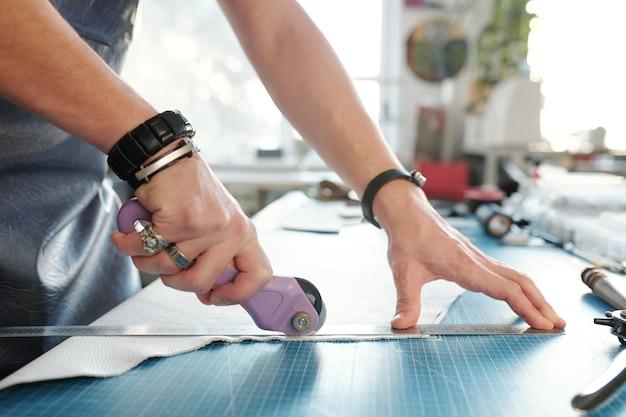 Handen van jonge creatieve professionele leerbewerker snijden stuk wit leer terwijl staande bij tafel in werkplaats