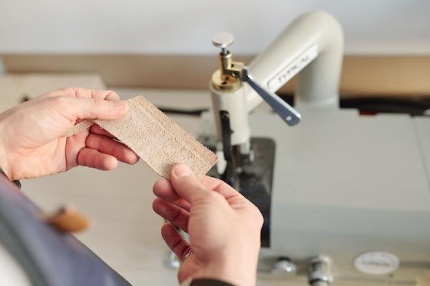 Handen van jonge creatieve vakman met klein stukje blond suède door elektrische machine tijdens het werkproces