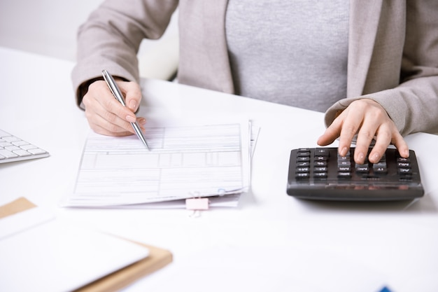 Handen van jonge elegante accountant met pen over financiële document knoppen van rekenmachine te drukken tijdens het werken door bureau