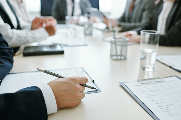 Handen van jonge elegante zakenman in het potlood van de kostuumholding op klembord met contract of ander document met collega's