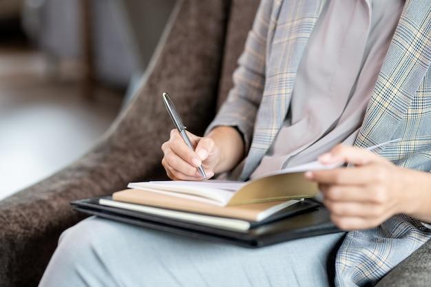 Handen van jonge elegante zakenvrouw met pen over pagina van voorbeeldenboek tijdens het maken van werkaantekeningen tijdens pauze