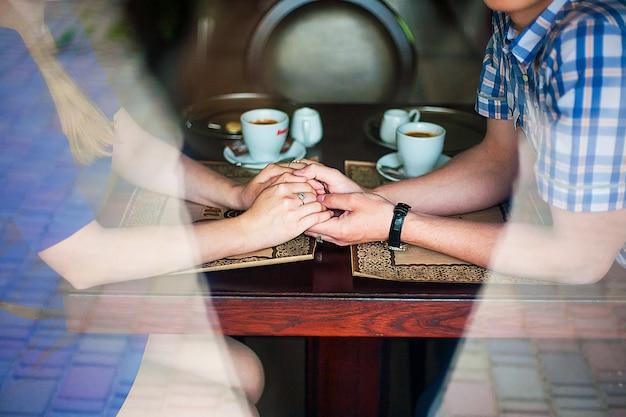 Handen van jonge geliefden met een warme kop koffie