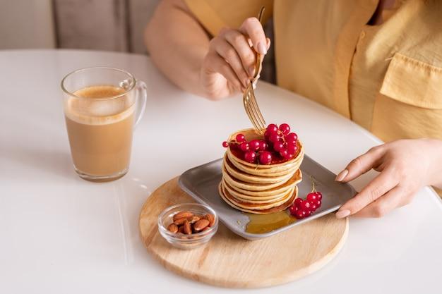 Handen van jonge hongerige vrouw aan tafel zitten en lekkere pannenkoeken met honing en verse rode bessen met cappuccino in café