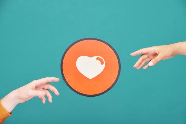 Handen van jonge man en vrouw reiken naar foto van wit hart in rode cirkel symboliseert liefde en genegenheid over blauwe muur