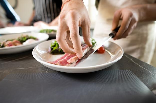 Handen van jonge man in schort die stuk gerookt of gegrild rundvlees op bord met groentesalade zet terwijl hij bij de tafel in de keuken staat
