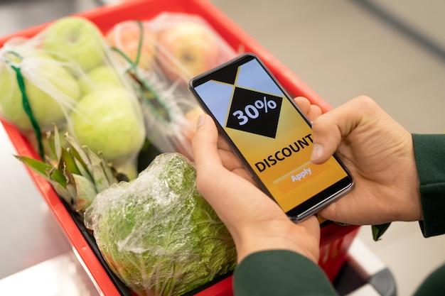 Handen van jonge man met smartphone met kortingsbon op het scherm over winkelwagentje met vers fruit en groenten
