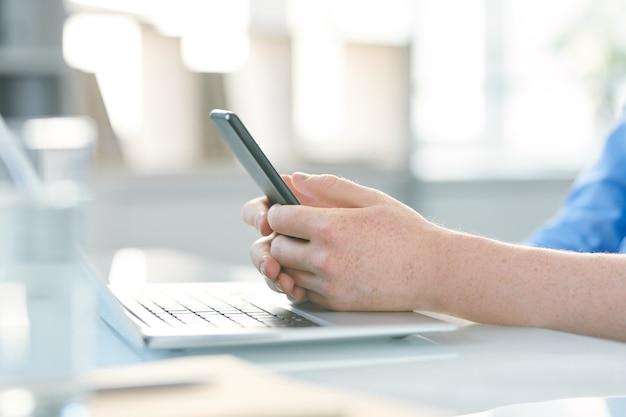 Handen van jonge manager met smartphone texting of scrollen op toetsenbord van laptop door bureau