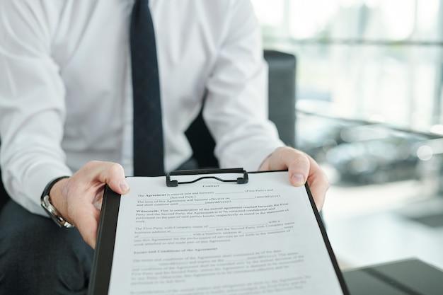 Handen van jonge manager van autocentrum met klembord met document van verkoop van een van auto's en klant aanbieden om handtekening te zetten