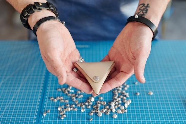 Handen van jonge mannelijke lederwerker die kleine driehoek beige lederen portemonnee houdt over blauwe tafel met stapel metalen knoppen