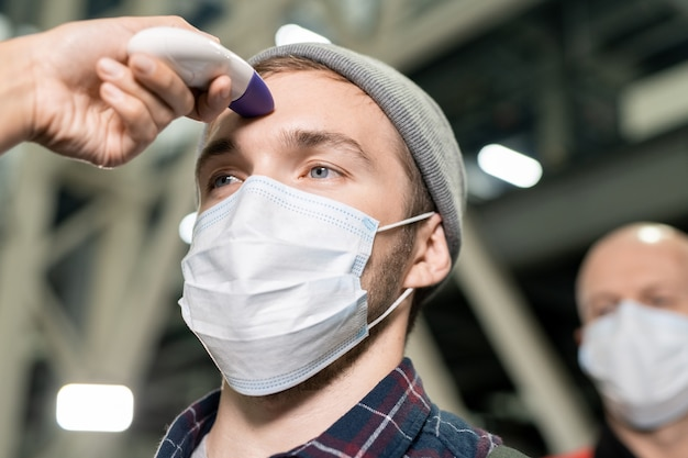 Handen van jonge medische werker met contactloze thermometer die de lichaamstemperatuur van ingenieurs met beschermende maskers voor het werk meet