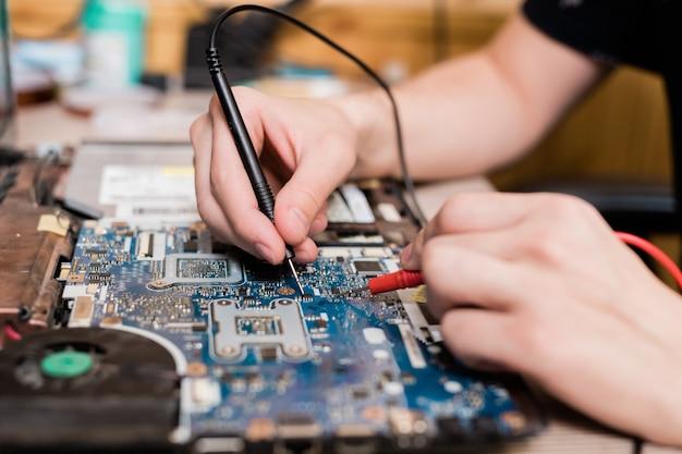 Handen van jonge meester van gadgetreparatieservice met behulp van twee kleine soldeerbouten tijdens het repareren van gedemonteerde laptop