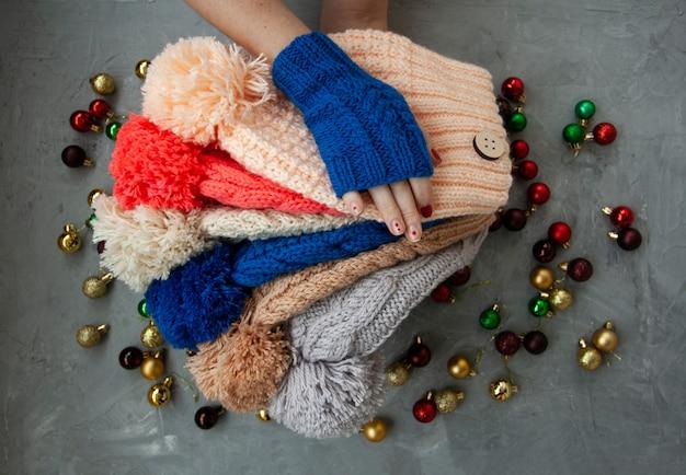 Handen van jonge mooie vrouw in blauwe wanten die vele gekleurde heldere warme de winterhoeden houden. op een grijze achtergrond zijn heldere kerstdecoraties.