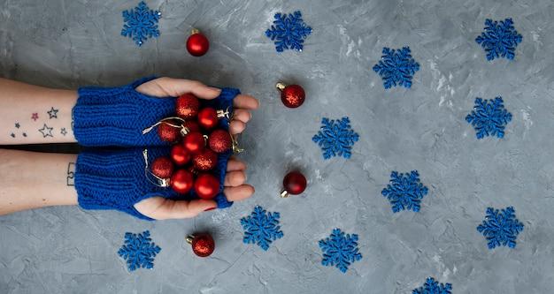 Handen van jonge mooie vrouw in blauwe wanten. ze houdt rode kerstballen vast. in de omgeving zijn blauwe sneeuwvlokken en rode decoraties op de kerstboom.