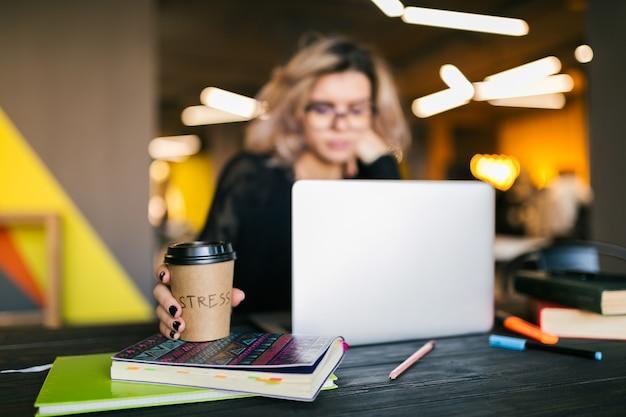 Handen van jonge mooie vrouwenzitting bij lijst in zwart overhemd die aan laptop in mede-werkend bureau, bezige student freelancer werken, die koffie drinken