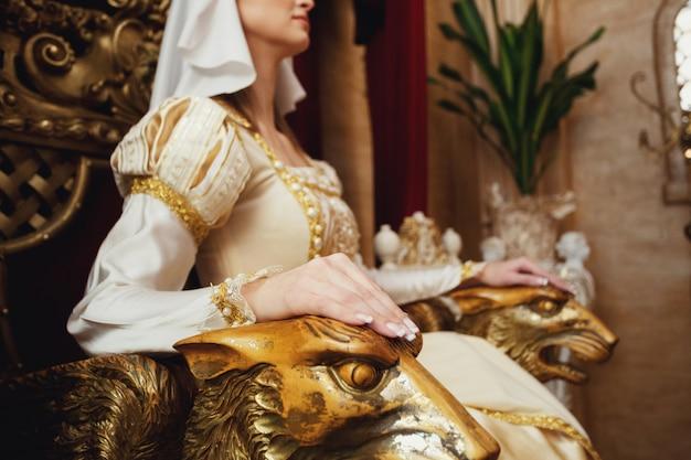 Handen van jonge prinses liggen op troon ellebogen, gemaakt als kattenhoofden