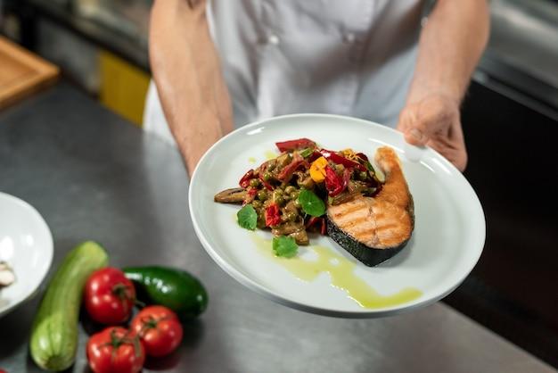 Handen van jonge professionele chef-kok met bord met stuk gebakken zalm en gestoomde gehakte groenten in de keuken