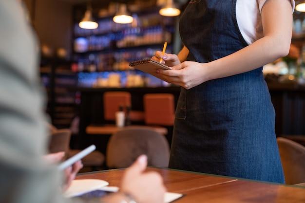 Handen van jonge serveerster in schort die de volgorde van de klant in kladblok opschrijft terwijl hij bij een van de tafels in café of restaurant staat