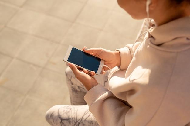 Handen van jonge sportvrouw in legging en hoodie luisteren naar muziek of online sporttraining in smartphone buitenshuis