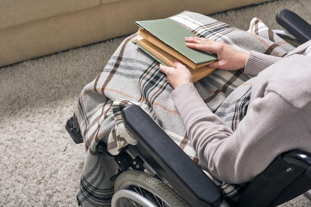 Handen van jonge uitschakelen vrouw met boek op haar knieën zittend in een rolstoel en tijd thuis doorbrengen