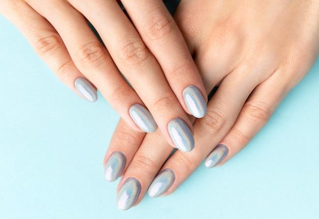 Handen van jonge volwassen vrouw met holografische modieuze nagels