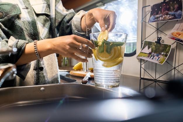Handen van jonge vrouw die gesneden citroen in kruik met water zetten