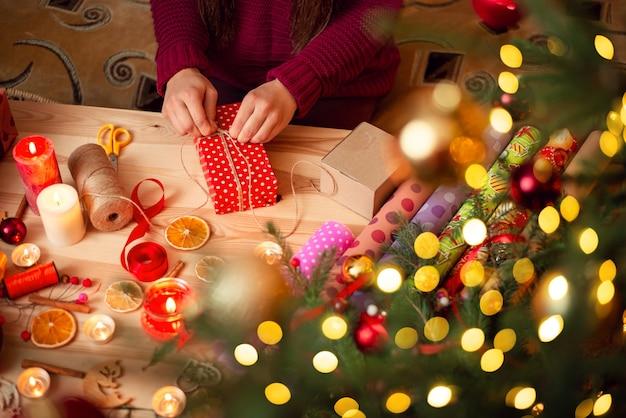 Handen van jonge vrouw die kerstcadeautjes voorbereidt voor vrienden en familieleden