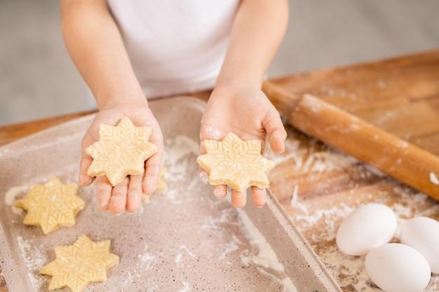 Handen van jonge vrouw die ruwe sneeuwvlokvormige koekjes houdt over dienblad op keukentafel bedekt met bloem