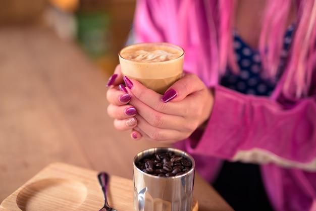 Handen van jonge vrouw koffie drinken en ontspannen in de coffeeshop