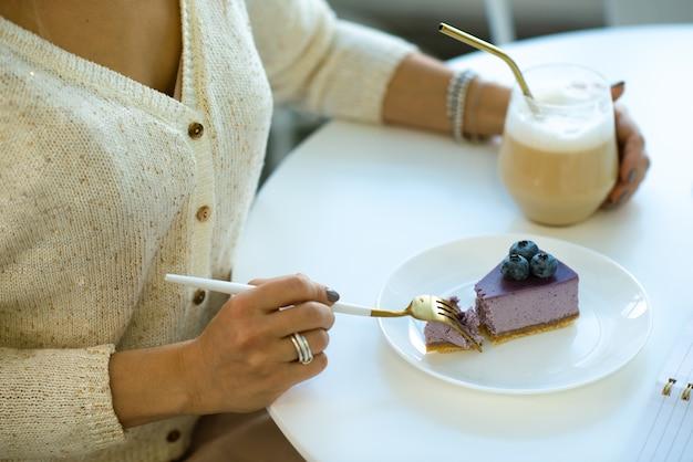 Handen van jonge vrouw met cappuccino en smakelijke bosbessenkaastaart eten zittend aan tafel in café
