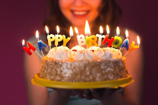 Handen van jonge vrouw met verjaardagstaart selectieve aandacht.