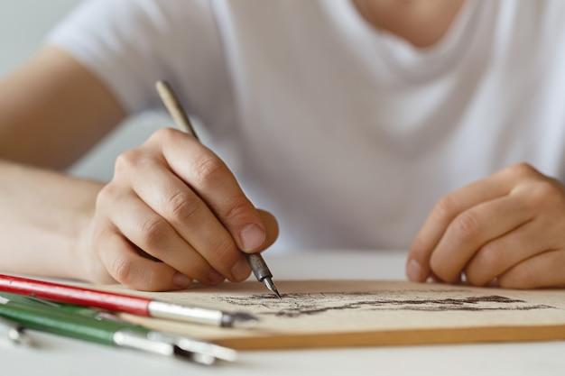 Handen van jonge vrouw met vulpen, schetsen in een album.