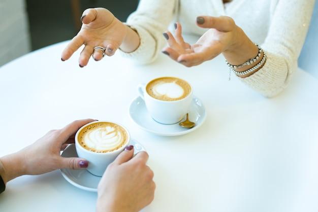 Handen van jonge vrouw praten met haar vriend vooraan terwijl zowel aan tafel zitten als verse cappuccino in café