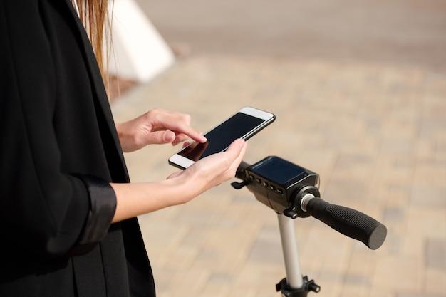 Handen van jonge vrouw scrollen in smartphone terwijl ze op een elektrische scooter staat en naar favoriete muziek luistert op weg naar haar werk