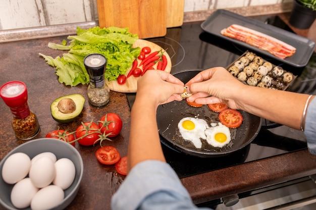 Handen van jonge vrouw verse kwarteleitjes breken op hete koekenpan tijdens het bereiden van ontbijt door elektrisch fornuis in de keuken