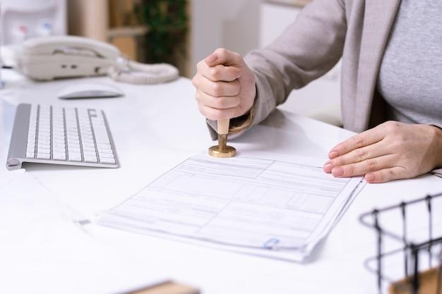 Handen van jonge vrouwelijke beambte die door bureau zit en zegel op financieel document zet alvorens het naar cliënt te verzenden