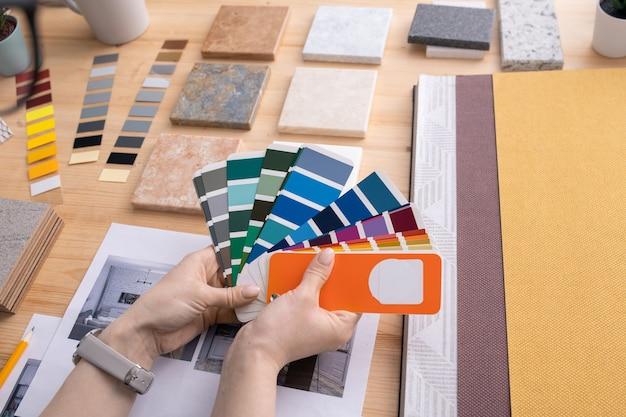 Handen van jonge vrouwelijke creatieve ontwerper die kleurenpalet met stalen boven tafel met monsters van panelen en behang