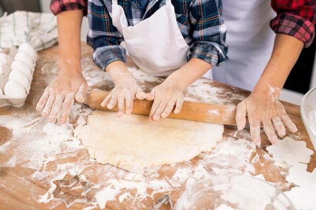 Handen van jonge vrouwelijke en kleine jongen die deeg op keukentafel rollen tijdens het samen bereiden van koekjes