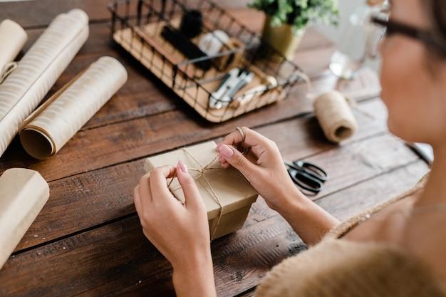 Handen van jonge vrouwelijke knoop van draden bovenop geschenkdoos