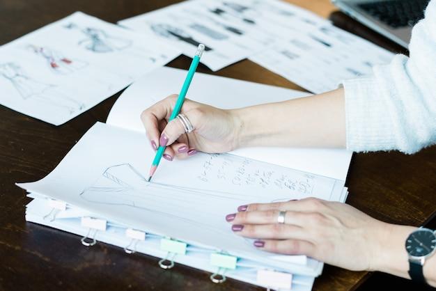 Handen van jonge vrouwelijke mode schets tekening op lege pagina van kladblok voor nieuwe seizoenscollectie zittend aan tafel